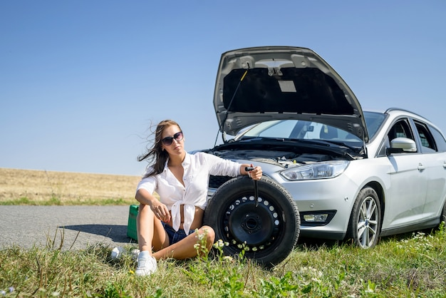Сексуальная красивая женщина и сломанная машина на дороге. проблемы с поездкой