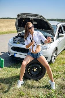セクシーな美しい女性と道路上の壊れた車。ロードトリップの問題