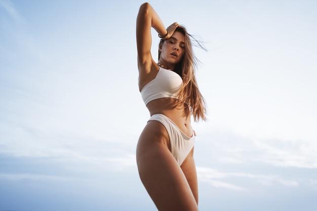 일몰에 바다 해안에서 흰색 수영복에 섹시 한 아름 다운 여자