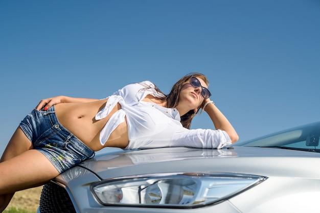 白いシャツとショートジーンズで車のボンネットに横たわっているセクシーな美しい女性。道路でお楽しみください