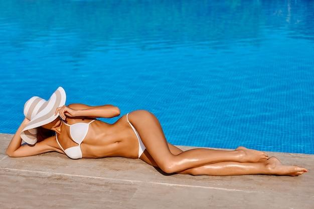 Sexy beautiful woman model in bikini is relaxing in swimming pool