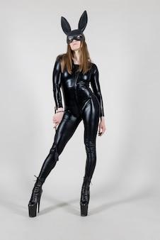 Сексуальная красивая женщина полюс танцор позирует в латексном костюме и черной маске кролика с кнутом на фоне. концепция пасхального кролика.