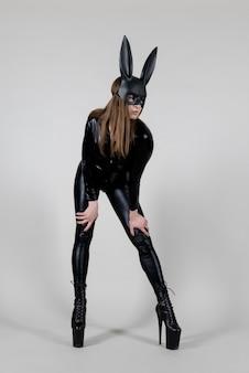 Сексуальная красивая женщина полюс танцор позирует в латексном костюме на фоне. концепция пасхального кролика.