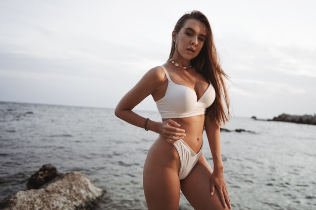Sexy beautiful woman in white swimwear at the sea coast on sunset