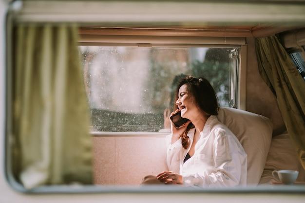 ベッドでスマートフォンを持つセクシーな美しい女性