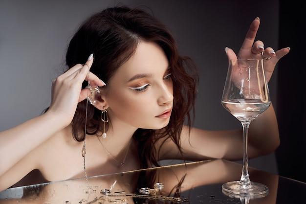 갈색 머리를 가진 섹시 한 아름 다운 여자입니다. 보석 반지 귀걸이. 완벽 한 여자 초상화입니다. 멋진 머리와 멋진 눈. 자연스러운 아름다움, 깨끗한 피부. 강하고 두꺼운 모발