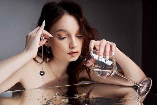 Сексуальная красивая женщина с каштановыми волосами. ювелирные кольца, серьги. идеальный женский портрет. великолепные волосы и красивые глаза. естественная красота, чистая кожа. сильные и густые волосы