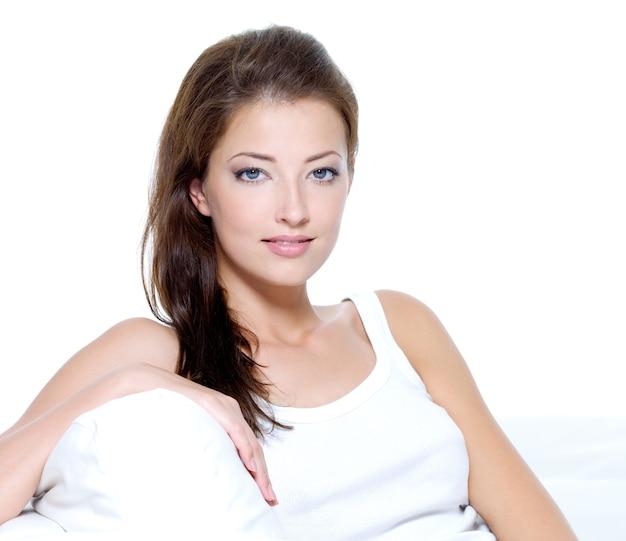 白で隔離のソファに座っているきれいな肌を持つセクシーな美しい女性