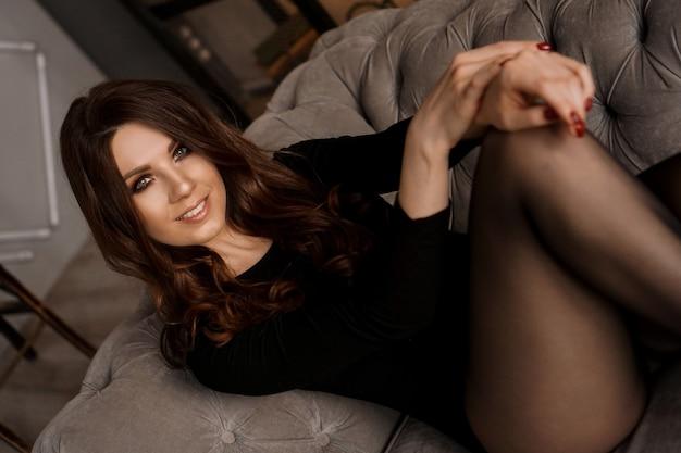 Сексуальная красивая женщина с длинными волосами и черными прозрачными колготками, лежа на диване