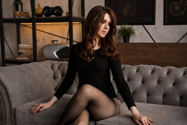 Сексуальная красивая женщина с длинными волосами и черными прозрачными колготками на диване