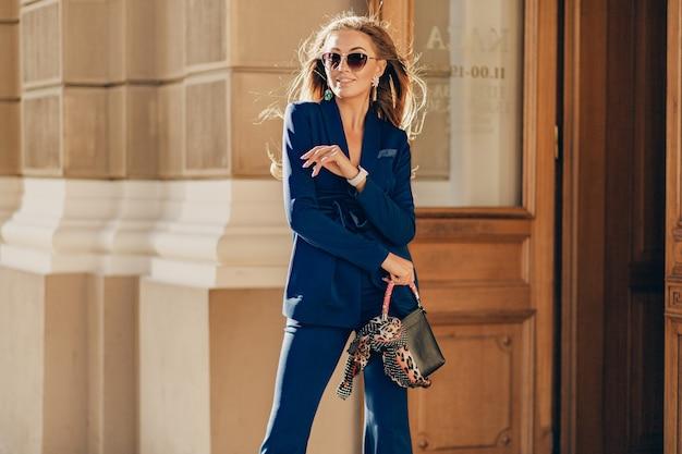 青いエレガントなスーツとサングラスを身に着けている通りで晴れた日に歩く長い髪のセクシーな美しい女性