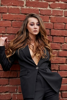 Sexy beautiful women. fashionable girl in a black suit near the brick wall. womens streetwear 2020. street style woman. how to dress this spring 2020