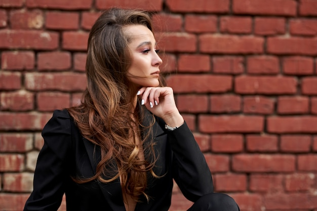 섹시한 아름다운 여성. 벽돌 벽 근처 검은 양복에 유행 소녀. 여자 스트리트 2020. 스트리트 스타일 여자. 2020 년 봄 옷 입는 법