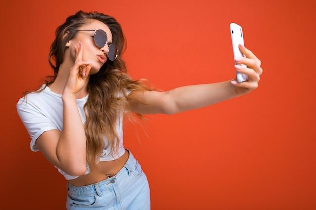 Сексуальная красивая молодая блондинка женщина, держащая мобильный телефон, делающая селфи фото с помощью камеры смартфона