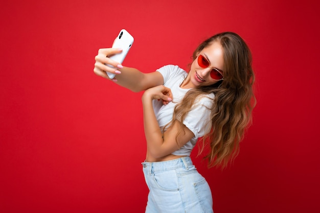 Sexy beautiful young blonde woman holding mobile phone taking selfie photo using smartphone camera