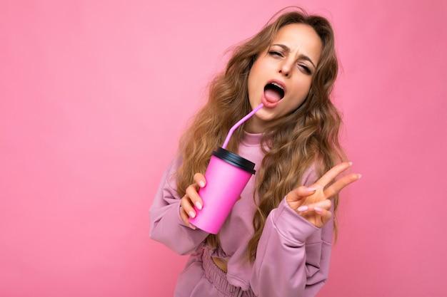 분홍색 스포츠 옷을 입고 섹시 한 아름 다운 젊은 긍정적 인 금발의 여자