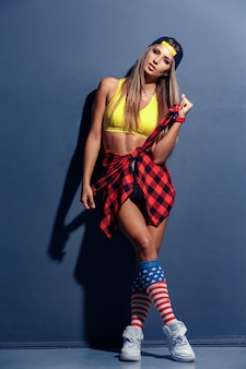 Sexy beautiful young woman model in sport shirt and hat, red checkered shirt, wristlet watch, white sneakers, leggings with usa flag, leaned on textured wall.