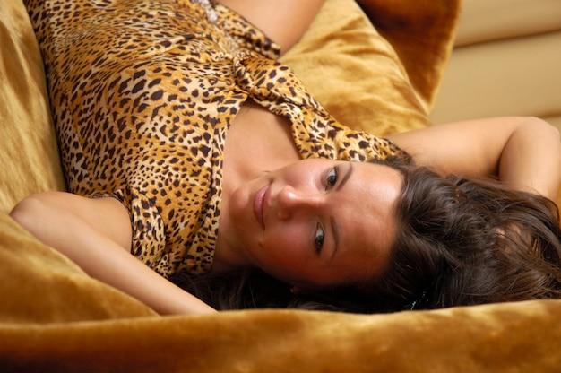 가죽 소파에 포즈 섹시 아름 다운 젊은 여자. 짧은 호랑이 드레스 소녀. 젊음, 매력 및 섹슈얼리티의 주제.
