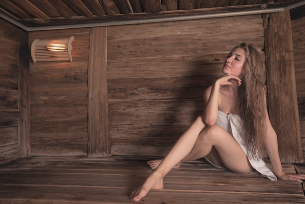 Sexy beautiful young woman sitting in wooden sauna