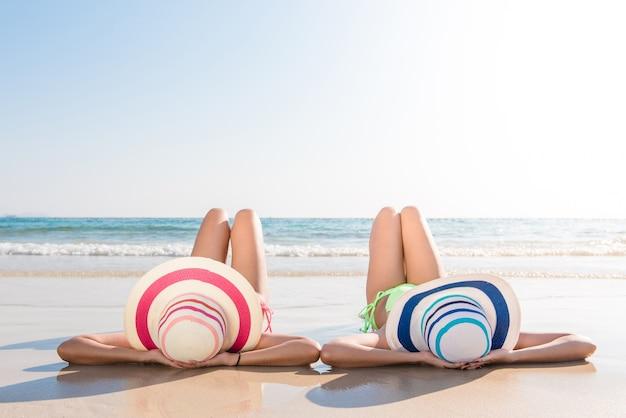 섹시한 비키니 바디 아시아 여성은 모자를 쓰고 해변의 모래에 누워서 바다를 즐기며 양쪽 다리를 공중에 올려 놓습니다. 행복한 섬 생활. 하얀 모래와 열대 해변의 크리스탈 바다.