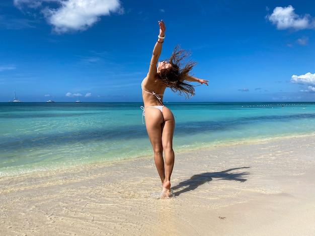 낙원 열 대 해변에서 두 팔을 벌려 자유에서 재미 섹시한 비키니 몸매 여자