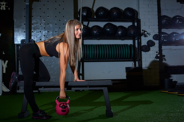 Sexy blond athletic woman in black tight leggings doing exercise on bench with weight cross-fit in the gym