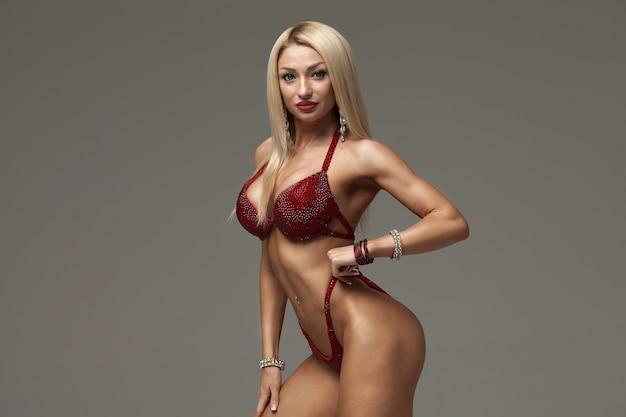 Sexy blond bodybuilder woman in bikini on grey background