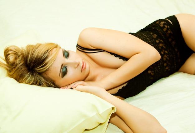 검은 란제리를 입고 침대에 누워 섹시한 금발 소녀