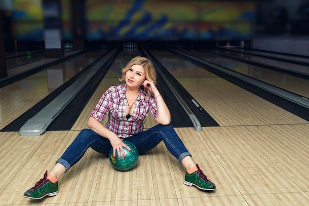 Сексуальная белокурая девушка сидит с мячом на полу в боулинг-клубе.