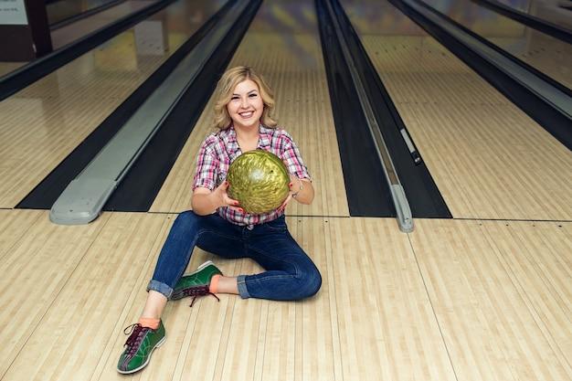ボウリングクラブの床にボールを持って座っているセクシーなブロンドの女の子。