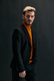 Сексуальный блондин в темной одежде и оранжевом свитере обрезал вид на черном фоне