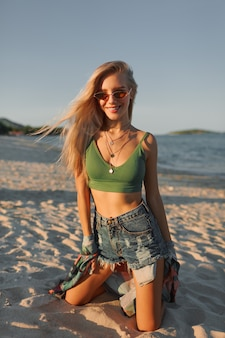 Sexy  blond woman in green crop top and jeans posing on tropical beach.