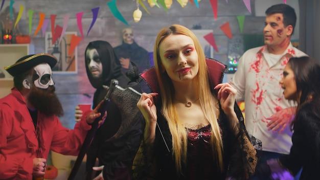 Bionda sexy in costume da maga che balla a una festa di halloween. gruppo di persone che celebrano halloween nella stanza decorata.