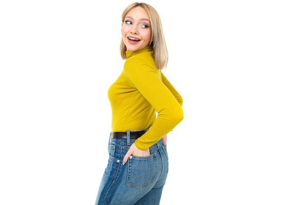 Сексуальная блондинка в облегающей лимонной блузке и джинсах позирует боком на белом фоне.