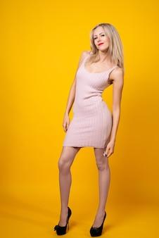 Сексуальная блондинка позирует на желтом в розовом коротком платье