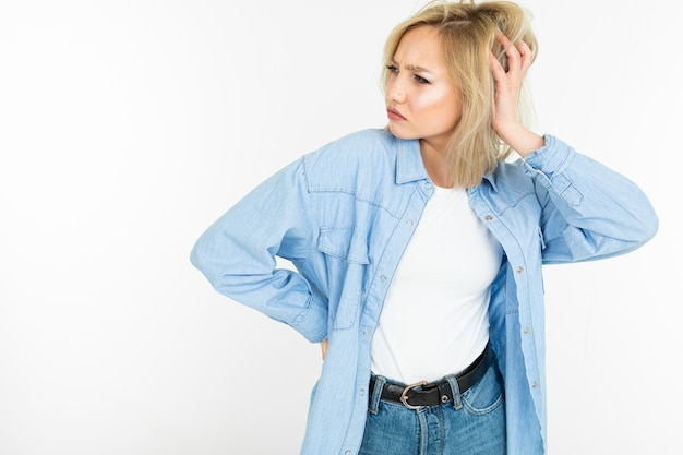 Sexy blonde girl in a stylish manner with a cotton shirt posing as a model on a white isolated background