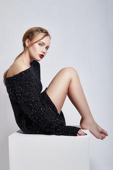 Sexy blonde girl in sweater sitting on cuba, portrait vivid makeup and lipstick closeup, facial cosmetics, professional makeup, skin care