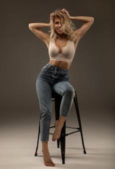 Сексуальная блондинка с пухлыми губами позирует в нижнем белье и джинсах.
