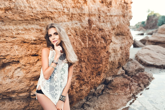 Sexy blonde girl with long hair is posing to the camera on rock background.