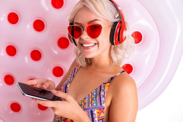 Сексуальная блондинка в купальнике слушает музыку в наушниках на белом