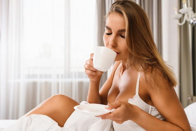 Сексуальная блондинка сидит в постели в белом кружевном бюстгальтере, держит белую чашку и блюдце, пьет горячий напиток на завтрак, наслаждается утром в солнечном свете в роскошном доме, отеле