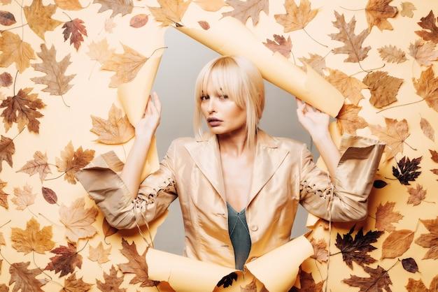 セクシーなブロンドの女性は秋の日の準備をしています。美しい官能的な女性のファッションの肖像画。秋の美しい女性は背景を残します。秋を祝います。