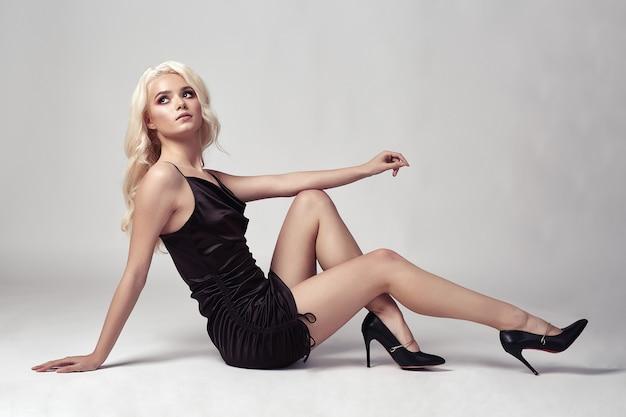 Sexy blonde woman in dress posing in studio