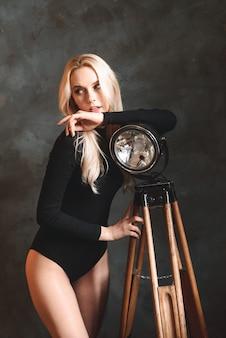 램프, 손전등 근처 집에서 bodysuit에서 섹시 한 금발 여자. 완벽한 몸매, 아름다운 몸매.