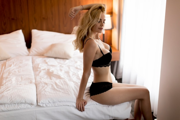 Sexy blonde woman in lingerie sitting on bed