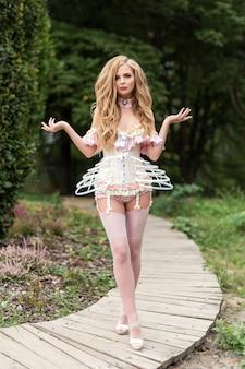 Сексуальная блондинка в красивом нижнем белье с чулками и корсетом гуляет в цветущем саду, горячая женщина в нижнем белье позирует чувственно на открытом воздухе на открытом воздухе женская фотомодель, подогнанная как кукла