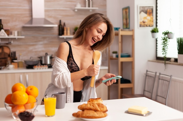 Sexy blonde young woman in lingerie drinking coffee sitting on table enjoing the morning. provocative young woman with tattoos wearing seductive underwear.