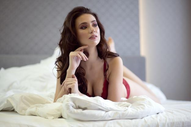 Сексуальная голубоглазая брюнетка в красном нижнем белье лежит на большой кровати
