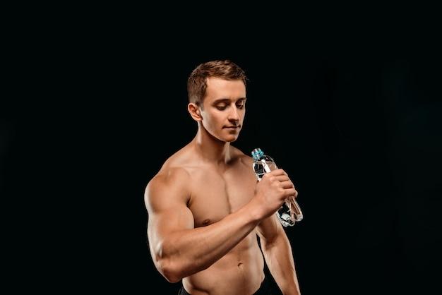 黒に分離された新鮮な水を飲んで筋肉胴とセクシーなボディービルダー