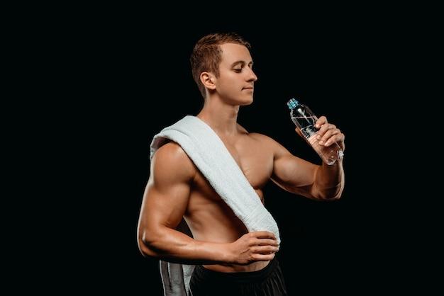 Сексуальный культурист с мускулистым торсом, держа полотенце и питьевой воды, сложенные